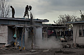 Cleaning the rooftops becomes necessary to maintain the houses, otherwise the roof would collapse from the weight of the ash, Tavurvur Volcano, Rabaul, East New Britain, Papua New Guinea, Melanesia, Pacific