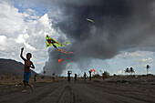Childern playing with kites in the volcanic ash, Tavurvur Volcano, Rabaul, East New Britain, Papua New Guinea, Pacific