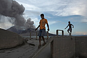 Children playing in the ruins of an old cement factory with erupting Volcano in the background. Tavurvur Volcano, Rabaul, East New Britain, Papua New Guinea, Pacific