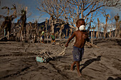 Poor children in the village collecting firewood. A dusk mask is something very precious. Tavurvur Volcano, Rabaul, East New Britain, Papua New Guinea, Melanesia- Pacific