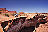 Jeep driving at brim above Colorado River, White Rim Drive, White Rim Trail, Island in the Sky, Canyonlands National Park, Moab, Utah, Southwest, USA, America
