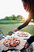 Woman cutting pizza, Klein Thurow, Roggendorf, Mecklenburg-Western Pomerania, Germany