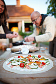 Man and woman preparing pizza in a garden, Klein Thurow, Roggendorf, Mecklenburg-Western Pomerania, Germany