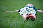 Boy lying in grass, Vienna, Austria