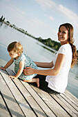Young mother and daugther on wooden jetty at Danube river, Old Danube, Vienna, Austria