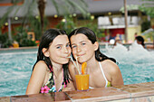 Two girls drinking juice in a pool, Bad Waltersdorf, Styria, Austria