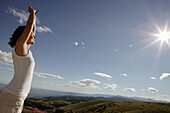 Woman stretching, landscape of hills in background, Tuscany, Italy