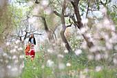 Zwei Mädchen laufen über Blumenwiese, Frau im Hintergrund, Esporles, Mallorca, Balearen, Spanien