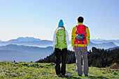 Young woman and young enjoying view over Kaiser range, Kampenwand, Chiemgau Alps, Chiemgau, Upper Bavaria, Bavaria, Germany