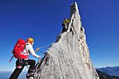 Young woman belaying climber at pinnacle, Kampenwand, Chiemgau Alps, Chiemgau, Upper Bavaria, Bavaria, Germany