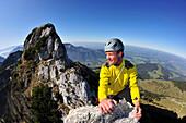 Young man reaching top of pinnacle, Kampenwand, Chiemgau Alps, Chiemgau, Upper Bavaria, Bavaria, Germany