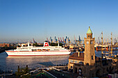 Cruise ship MS Deutschland entering port at the tower of St. Pauli Landungsbrücken, Hamburg, Germany, Europe