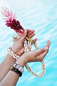 Close-up of woman's hands holding flowers and sea shell necklace