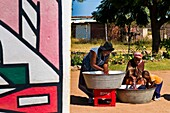 Africa, South Africa, Mpumalanga Province, KwaNdebele, Ndebele tribe, Mabhoko village, house of the artist Francina Mbonani, her daughters Bleji and Letty washing clothes helped by the young Sanelisiwe