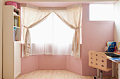 Small room with a bay window, and net curtains. Pink painted walls and wooden floor. Desk and chair. Domestic interior., Hsinchu city, Taiwan, Asia.