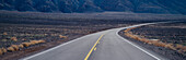 A highway curving through desolate area of Death Valley National Park, California, Highway in Death Valley National Park