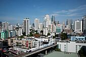 A mass transit train passes through Bangkok downtown business district. Modern architecture. Skyscrapers. Public transport., Bangkok, Thailand. City skyline and mass transit train