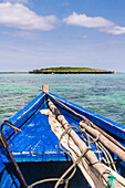 A traditional fishing boat in the emerald sea of Antsiranana (Diego Suarez), north of Madagascar. Mast, sails and rigging laid on the deck. An islet in the sea., Traditional fishing boat