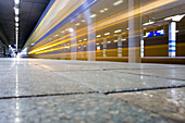 An intercity train passing through a railway station at speed. Motion blur., Intercity