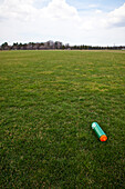 A sports ground, grass field, with trees on the horizon.  A water bottle on the ground., A Water Bottle on a Sports Field
