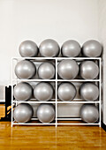 A group of inflatible fitness balls, silver coloured, stacked up in a rack. A gymnasium., Exercise Balls in a rack
