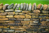A close up of a traditional construction, a dry stone wall, with stones built up without mortar. Top stones places vertically., Detail of stone wall on Mainland Orkney Islands Scotland