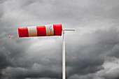 Red and white wind vane. Wind sock, weather indicator at an airfield.  Windblown, at vertical level in stormy weather. Indicating the wind direction. Dark storm clouds in the sky., Wind Vane in stormy weather
