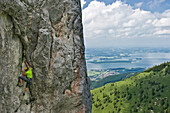 Rock climber ascending Kampenwand, Lake Chiemsee in the background, Chiemgau, Bavaria, Germany