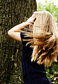 Young Blond Girl Standing Against Tree Trunk, Rear View