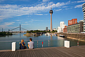 Couple sitting on a bridge at media harbour, view to Rhine tower and Neuer Zollhof, Duesseldorf, North Rhine-Westphalia, Germany, Europe