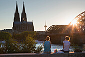 Young women sitting on the Rhine river banks opposite to the cathedral, Cologne, North Rhine-Westphalia, Germany, Europe