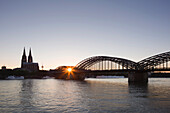 View over the Rhine river onto the cathedral and Hohenzollern bridge at sunset, Cologne, North Rhine-Westphalia, Germany, Europe