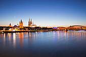 View over the Rhine river onto the old town with town hall, church Gross St Martin, cathedral and Hohenzollern bridge in the afterglow, Cologne, North Rhine-Westphalia, Germany, Europe