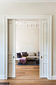 View through sliding door into a living room with oak floorboards of an old building flat, Hamburg, Germany