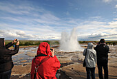 Tourists taking photos of the Strokkur geyser in the valley of Haukadalur at the golden circle, Iceland, Europe