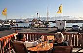 People in a cafe at the harbour, Husavik, North Iceland, Europe