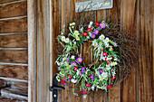 Blumenkranz hängt auf Holztüre an altem Bauernhaus, Strassberg, Walserweg, Arosa, Graubünden, Schweiz