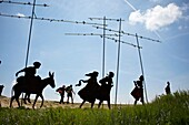 Two pilgrims walk past metal sculpture silhouettes of pilgrims on the Camino de Santiago, near Pamplona, Spain