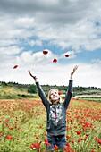 Blonde teen girl throwing flowers in the wind.