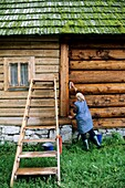 Poland, Zakopane region, Chocholow, Woman sprucing up her house prior to Corpus Christi festival  This very ancient tradition takes place twice a year, for Corpus Christi and Christmas and lasts several days  Once, a highlander would judge whether a poten
