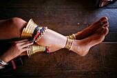 Closeup of a girl´s legs adorn with bangles and traditional jewelry Approximately 300 Burmese refugees in Thailand are members of the indigenous group known as the Longnecks The largest of the three villages where the Longnecks live is called Nai Soi, lo