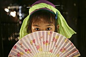 A young Longneck girl hides behind her fan Approximately 300 Burmese refugees in Thailand are members of the indigenous group known as the Longnecks The largest of the three villages where the Longnecks live is called Nai Soi, located near Mae Hong Son Ci