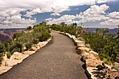 A paved walkway leads to the precipice overlooking the Grand Canyon