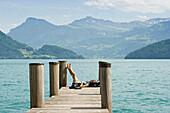 Female hiker sitting on a landing stage in Weggis, Lake Lucerne, canton Lucerne, Switzerland, Europe