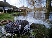 Flood coming up through sewer, River Lavant flooding, West Sussex, England