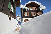 Child pulling a sledg through Gargellen, Montafon, Vorarlberg, Austria
