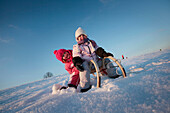 Two children sledding, Kammerloh, Muensing, Bavaria, Germany