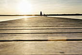Woman standing on a jetty at lake Starnberg, Upper Bavaria, Germany
