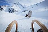 Couple sledding downhill, Kuehtai, Tyrol, Austria