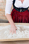 Woman dressed in traditional clothes making sourdough, Baking bread, homemade, Bavaria, Germany